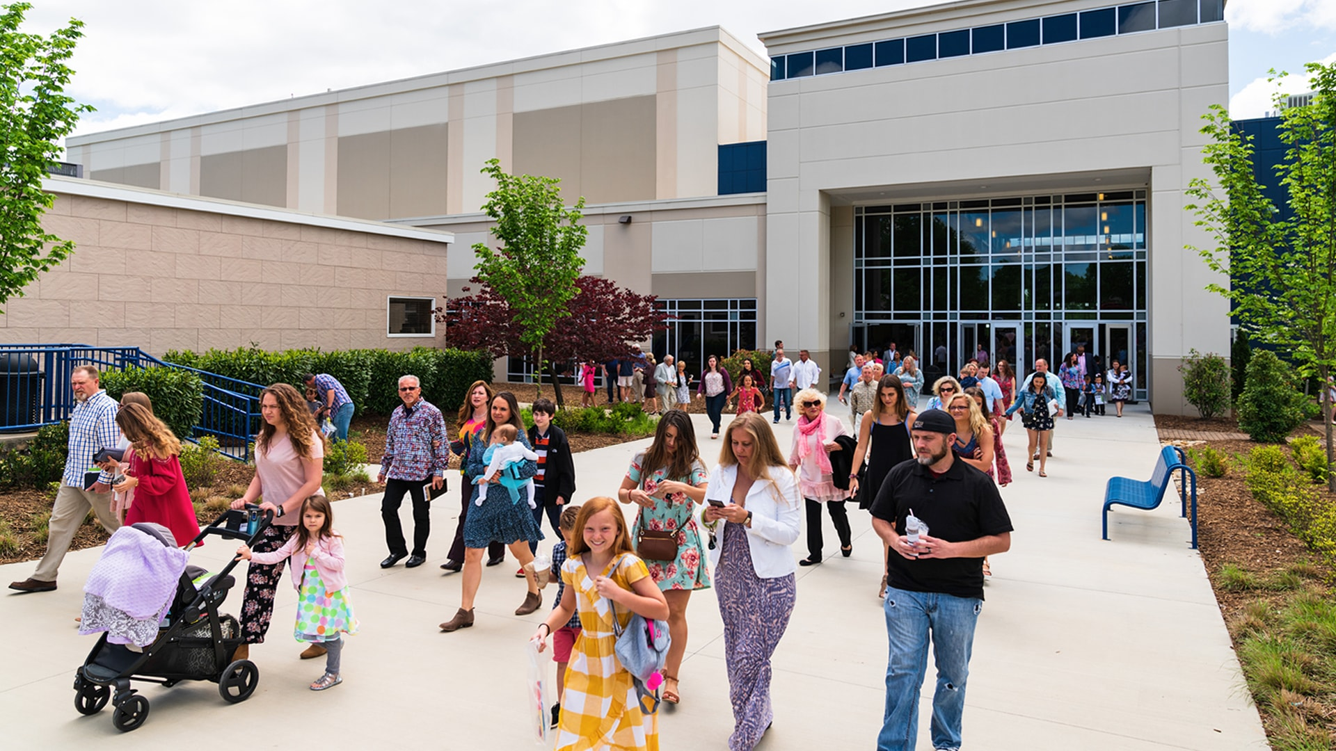 A crowd of all different ages and walks of life leaving the Brookwood Church building after a service