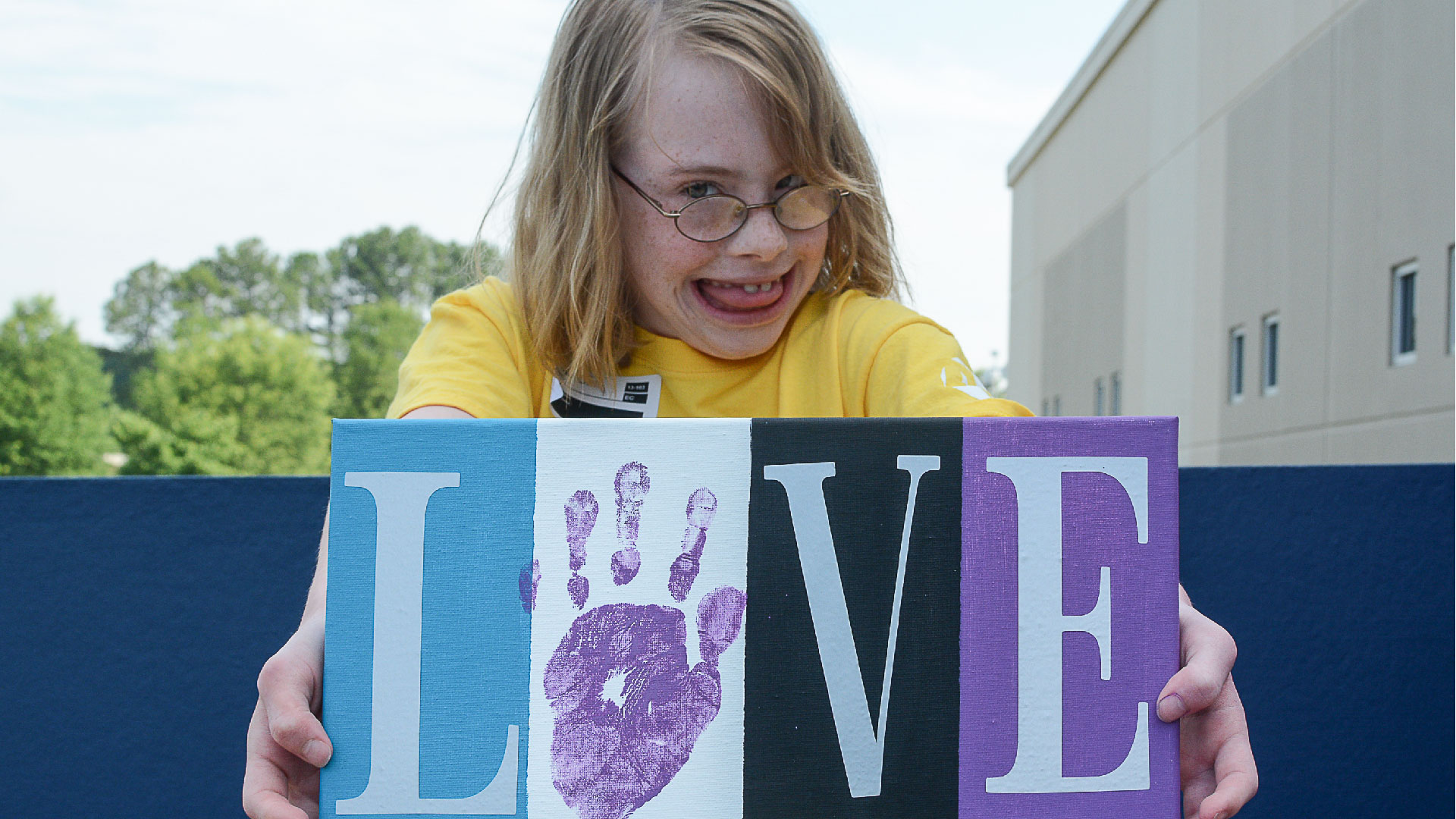 Special Needs member holds up a picture that says Love at Brookwood Church