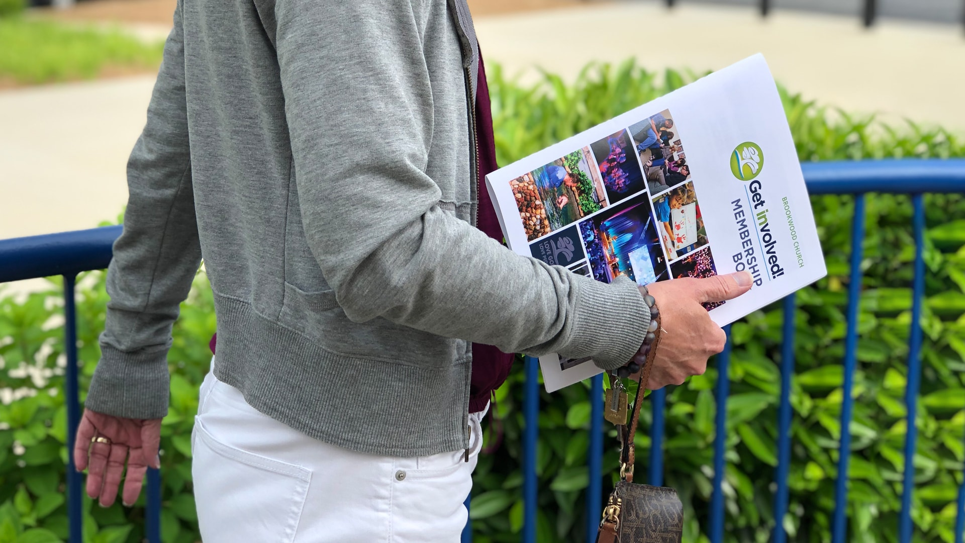 A woman carrying the Get Involved! membership booklet outside of Brookwood Church