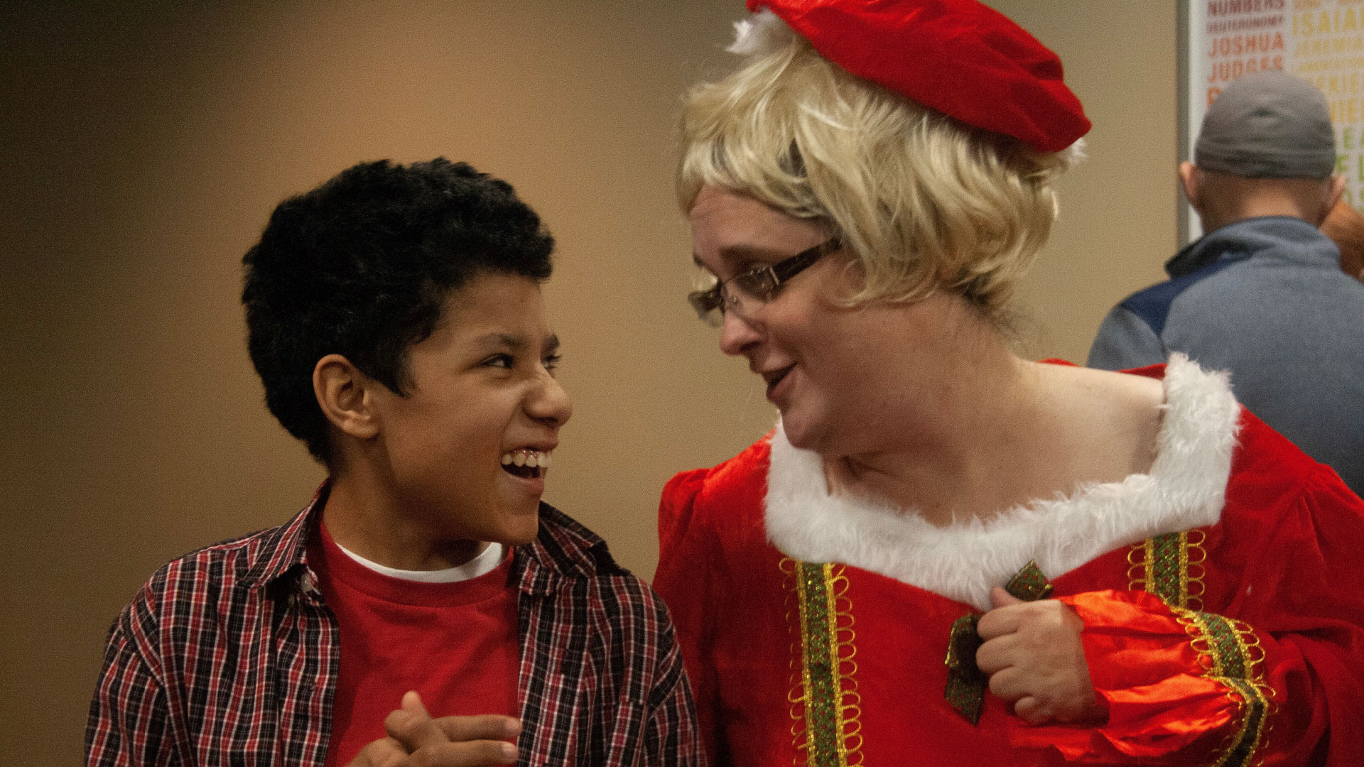A volunteer dressed up at a Special Friends event at Brookwood Church interacts with a smiling Special Friend.