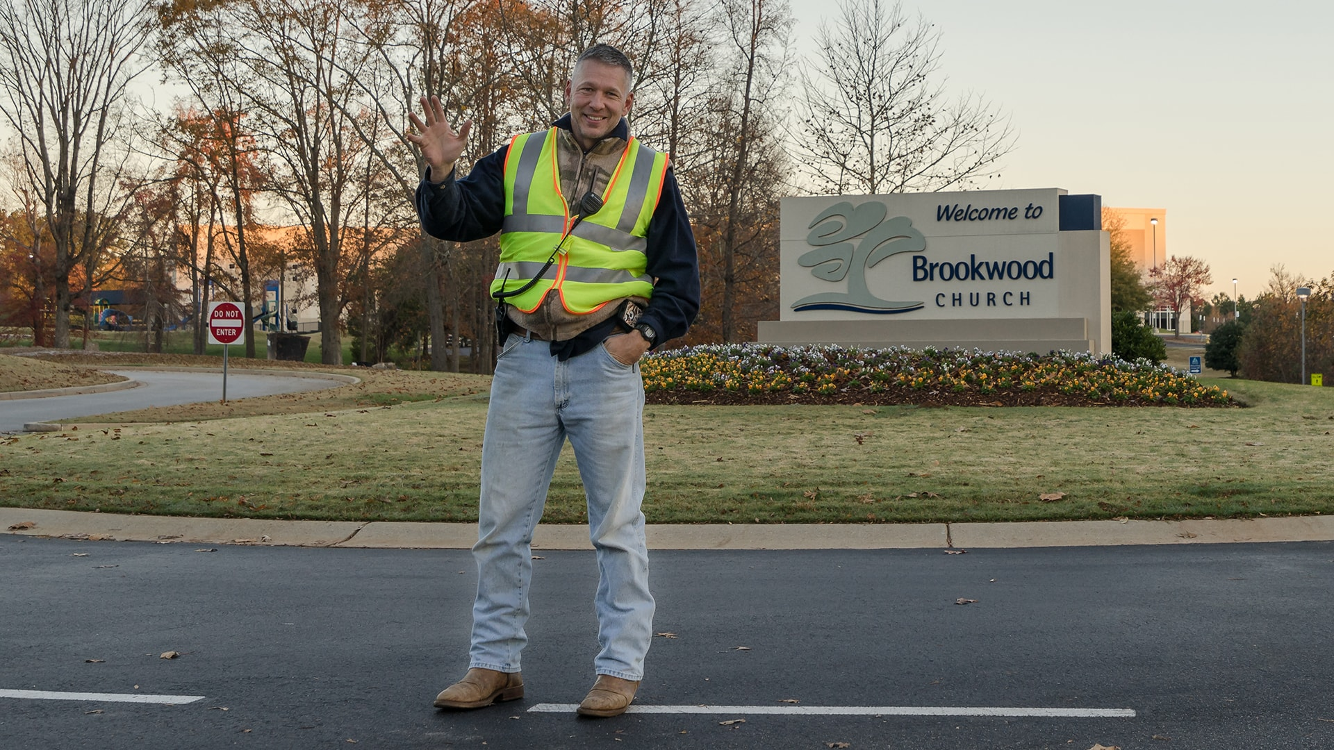 A member of the Brookwood Church Traffic Team smiling and waving.