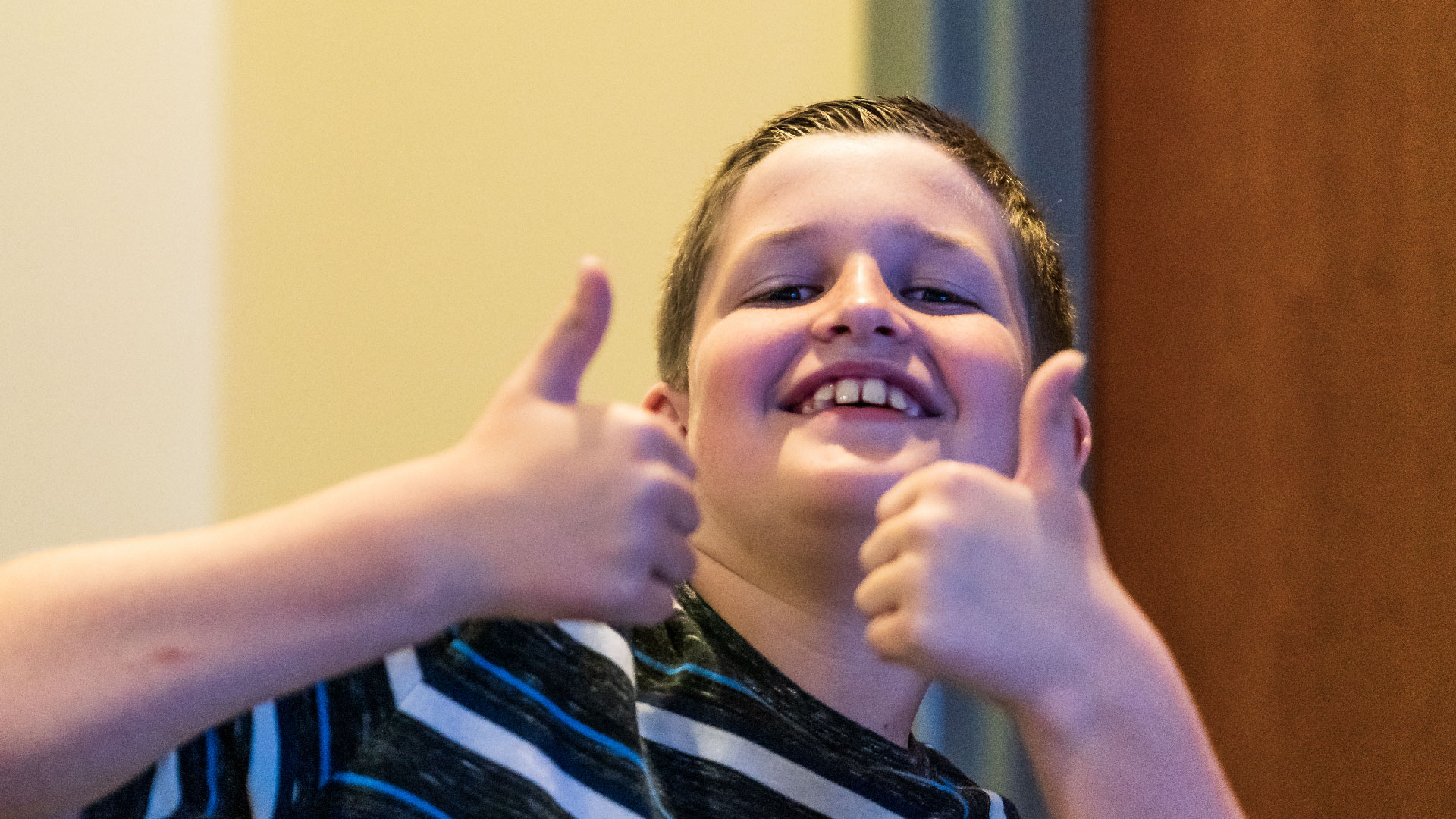 A child smiling holding two thumbs up at Brookwood Church
